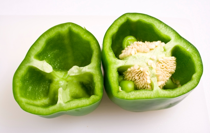 Fresh green pepper halves on a clean white background