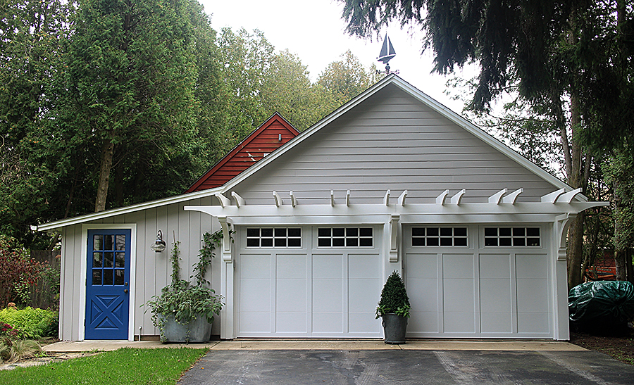 White garage with planters in front.