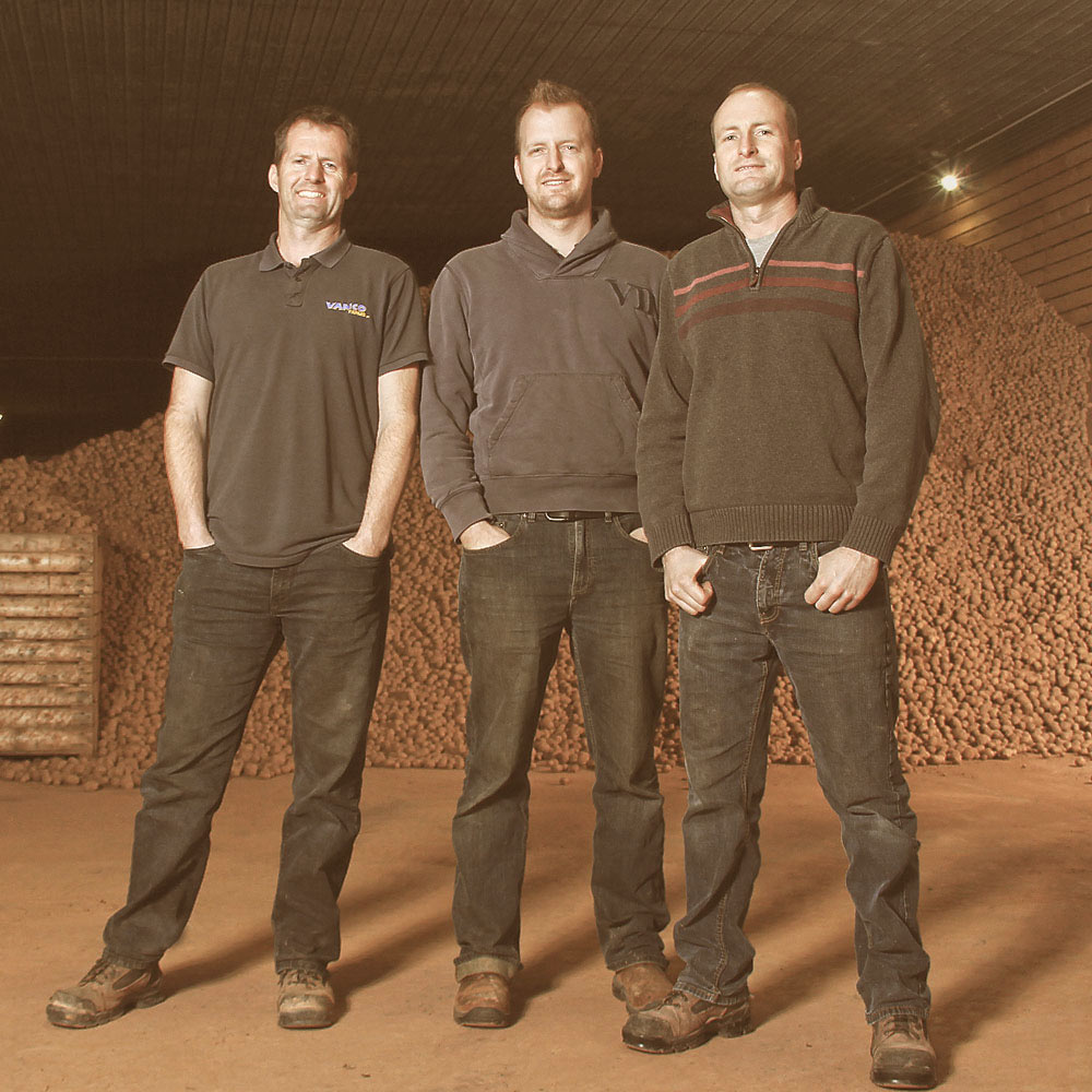 three Van Nieuwenhuyzen brothers, owners of Vanco Farms, in front a a huge pile of potatoes.