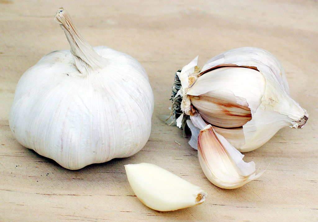 White garlic bulb and garlic bulb being broken up into cloves. Two cloves are shown.