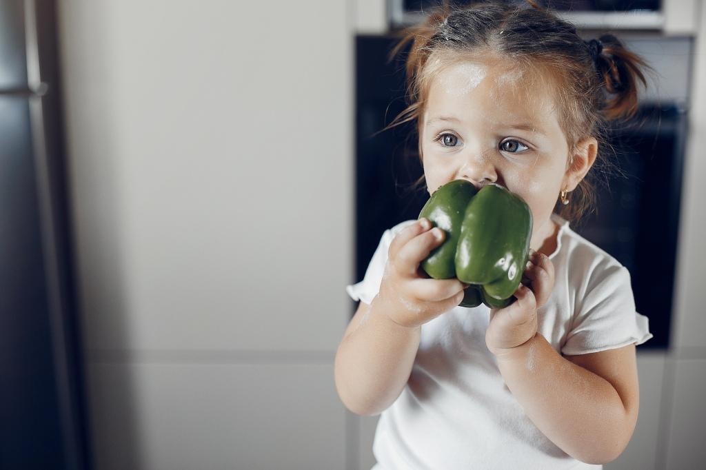 Little girl eating green pepper, kitchen