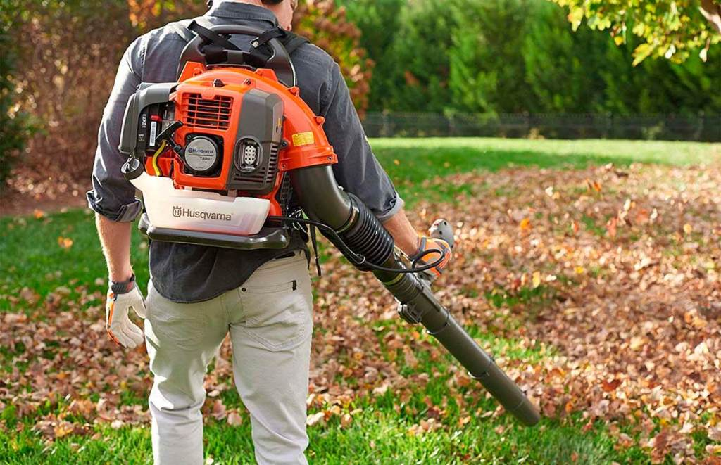 Man using leaf blower to push leaves.