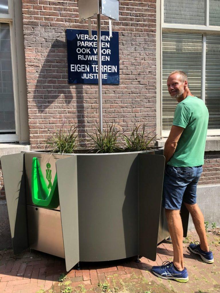 Man urinating into a GreenPee planter.