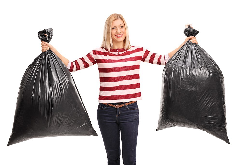 Woman holding two full trash bags sealed.