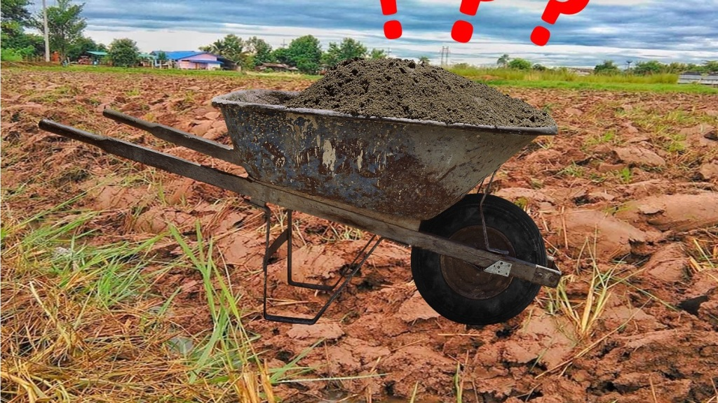 Wheelbarrow of sand on top of red clay soil, with question marks indicating doubt.