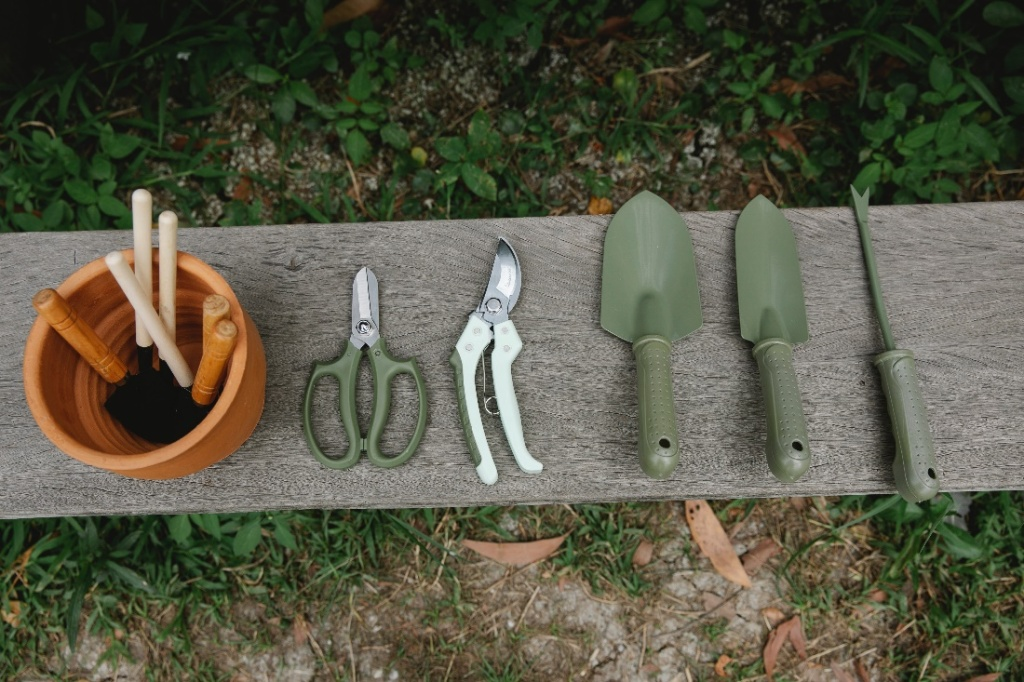 Gardening tools displayed on a wood beam.