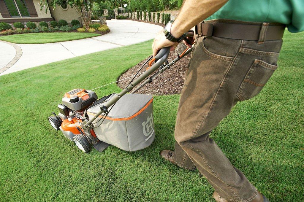 Man pushing lawn mower.