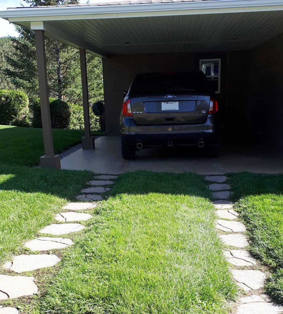 Driveway with pavers for tire traffic and sod down the middle.