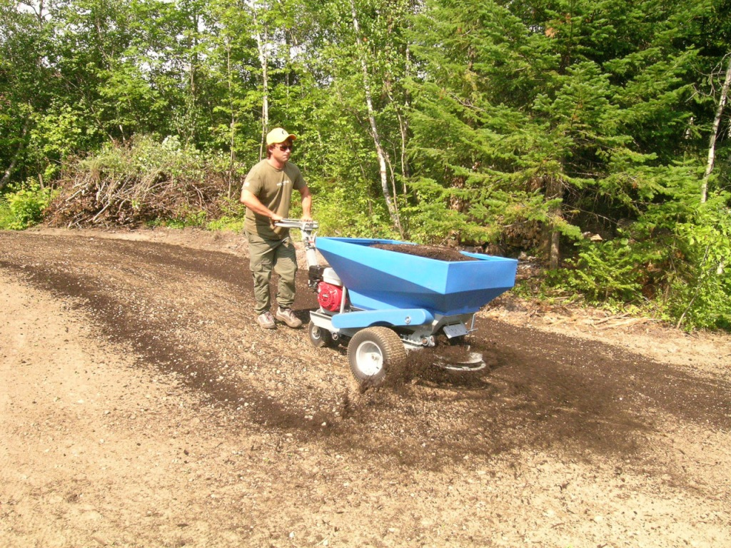 A motorized top-dresser applying compost to a field.